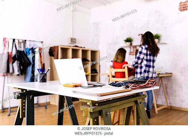 Laptop in studio with two fashion designers in background
