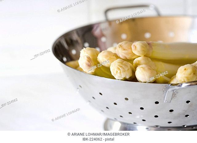 Raw and washed asparagus in a sieve