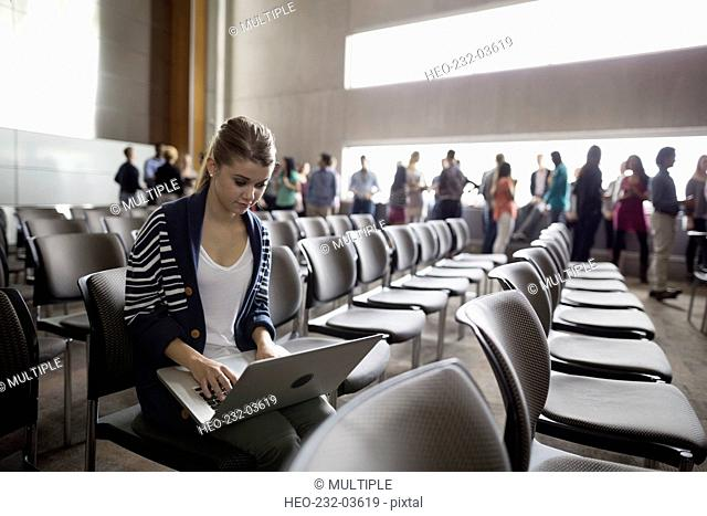 Student using laptop in auditorium seat