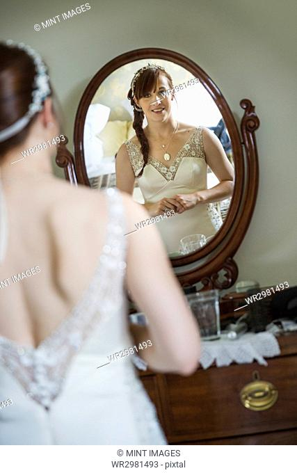 Smiling bride in her wedding dress looking at herself in a mirror