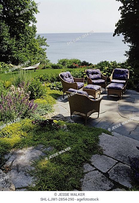 GARDEN/ PATIO: Terraced stone patio and walkway overlooking waterviews and garden, wicker patio furniture, hammock