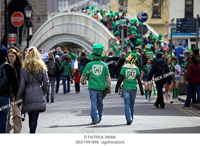 crowds of people walking down the street many wearing green celebrating saint patrick's day, county dublin ireland
