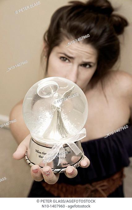 Teen girl holding a glass globe