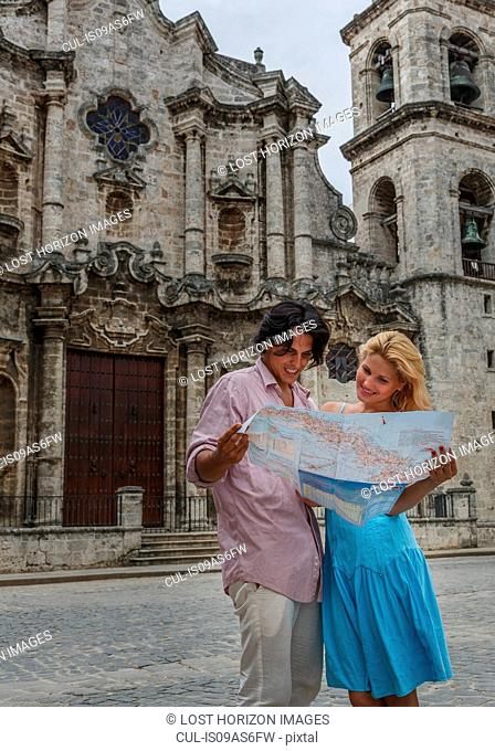 Young couple with map in the Plaza de la Cathedral of Havana, Cuba