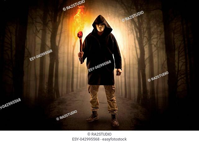 Mysterious man coming from a path in the forest with burning flambeau concept