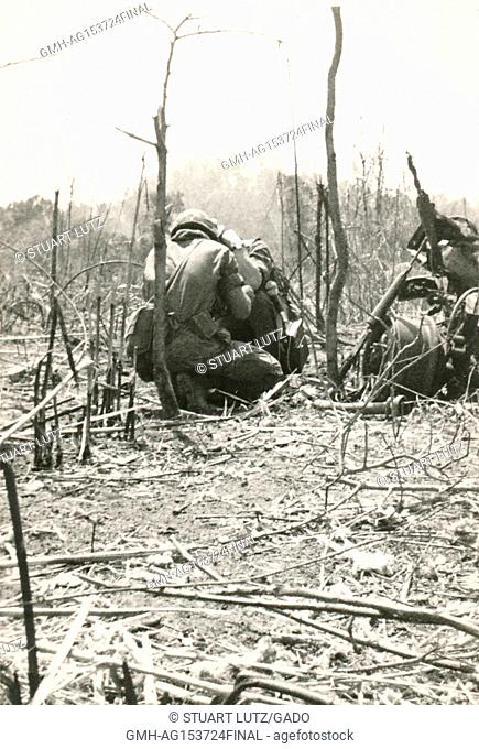 American servicemen crouch down in a line and operate a machine gun in the jungles of Vietnam during the Vietnam War, 1968. ()