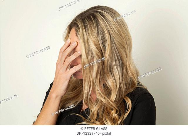 Woman With Blond Hair Hiding Her Face With Her Hand; Connecticut, United States Of America
