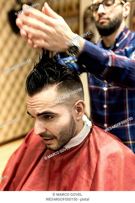 Hairdresser styling young man's hair in a barbershop
