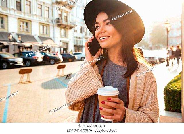 Portrait of a joyful stylish woman talking on mobile phone while walking outdoors with a coffee cup