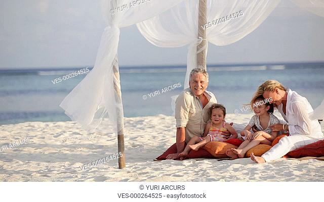 Portrait of a happy mature couple with their sweet llittle girls sitting on a beach together