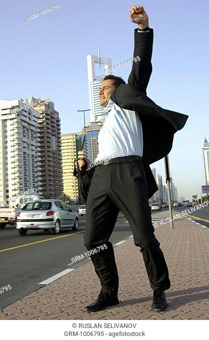 Jubilating businessman on Sheikh Zayed Road in Dubai