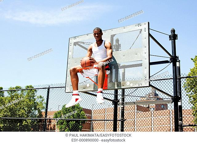 Handsome sporty African-American male basketball player dressed in white and holding his ball outdoor on a summer day in a basketball court while sitting in the...