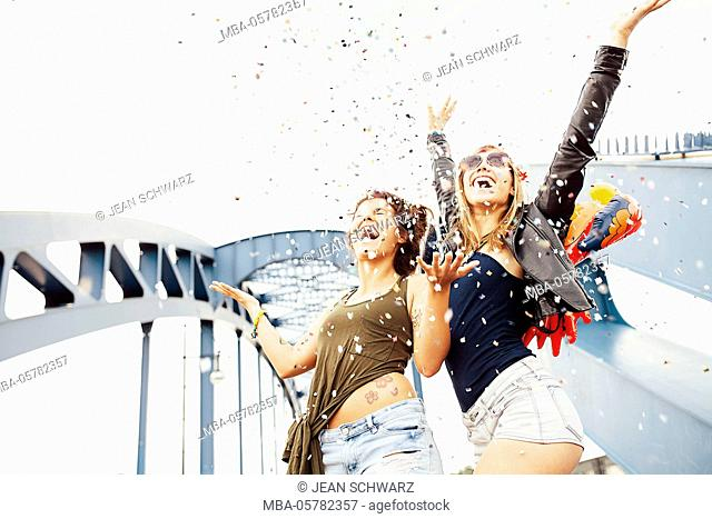 Two young women throwing confetti into the air and looking up