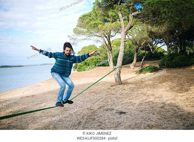 Young man with dreadlocks practicing on a slackline