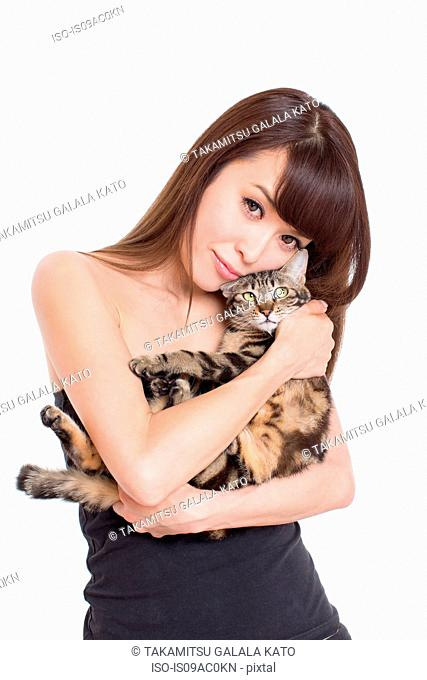 Portrait of woman holding tabby cat