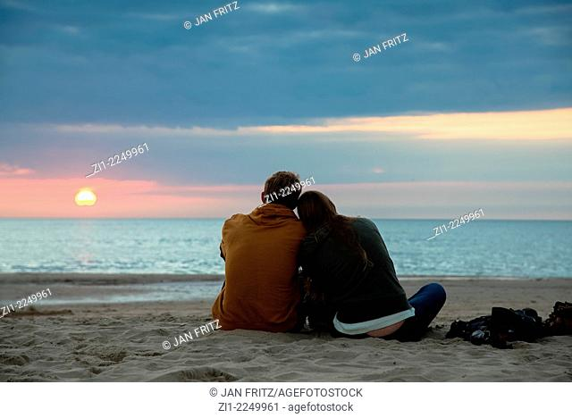 A couple sitting on the sand at the beach enjoying the sunset