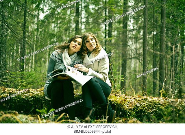 Caucasian women reading magazine in forest