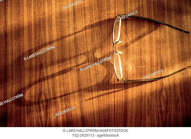 Eyeglasses on wooden table with shadow of the glasses on the surface
