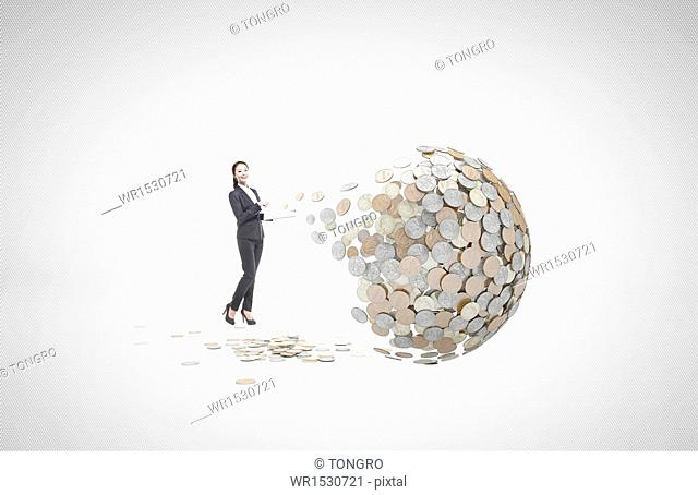 a business woman standing next to a ball of coins