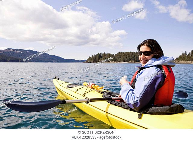 Woman sea kayaking in Kachemak Bay, near Homer, South-central Alaska; Alaska, United States of America