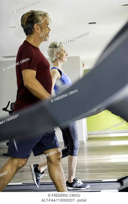 Man and woman exercising on treadmills