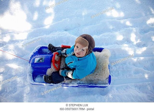Child riding toy snowmobile in snow