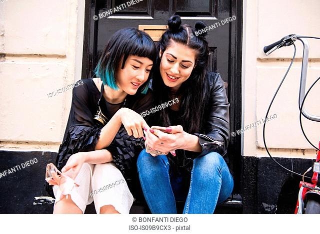 Two young stylish female friends sitting doorstep looking at smartphone