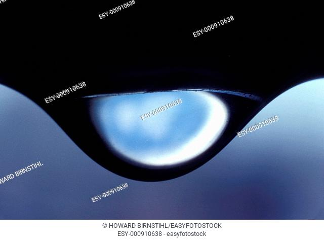 extreme close up of a water droplet hanging in suspension about to fall