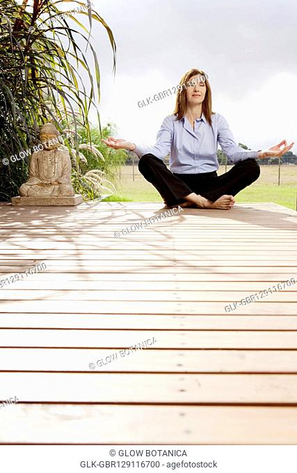 Businesswoman doing yoga in a park