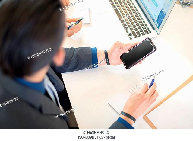 Businessman looking at smartphone at desk