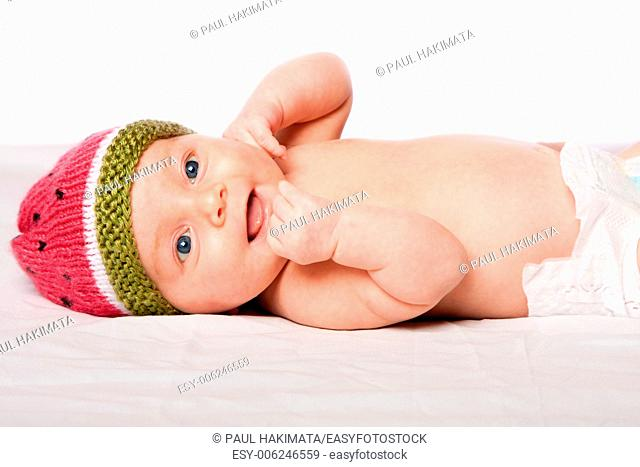 Happy smiling baby infant face with knitted watermellon hat laying on white