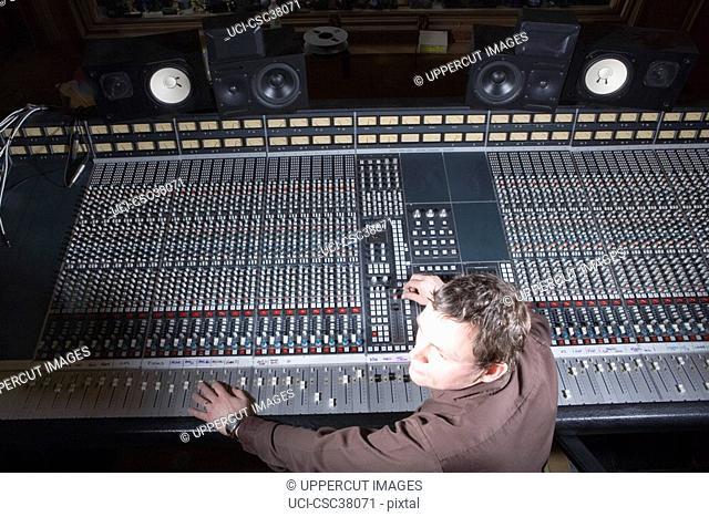 Producer adjusting sound equipment