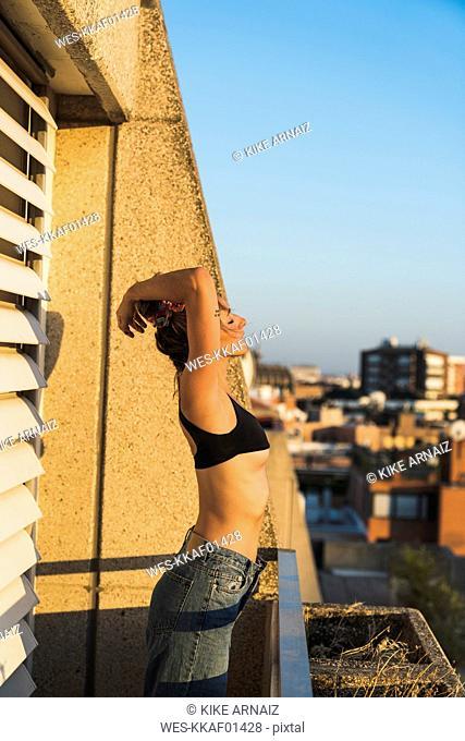 Young woman wearing bra standing on balcony