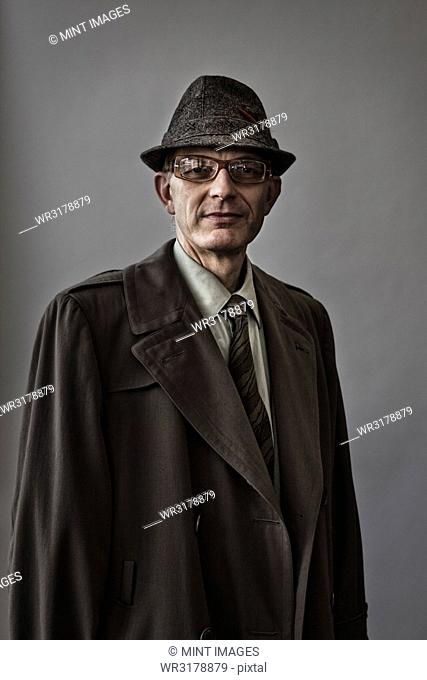 Studio portrait of Caucasian man actor with a hat and overcoat on