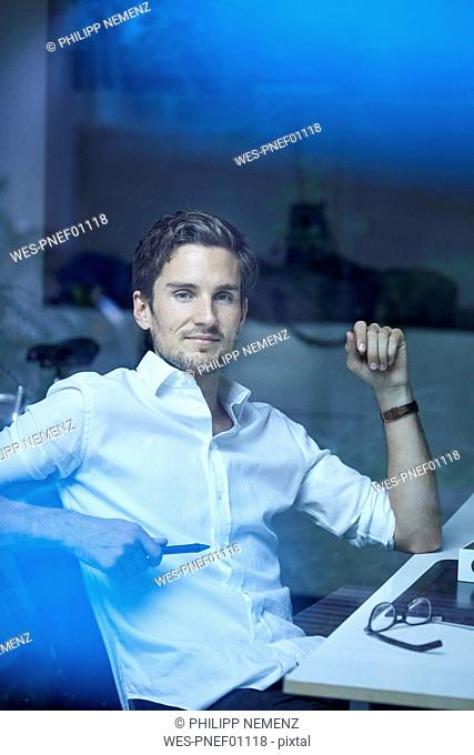 Portrait of successful young businessman behind windowpane at his office desk