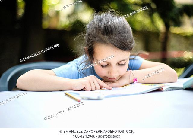Girl reads on the table in the garden