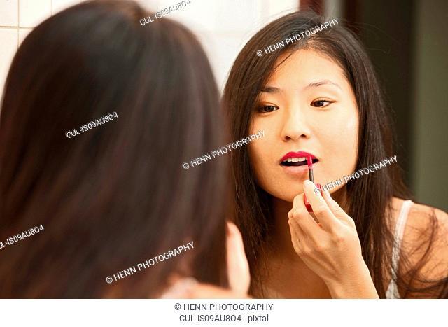 Mid adult woman applying lip gloss