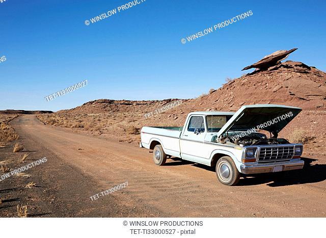 USA, Arizona, Broken pick-up truck on desert road