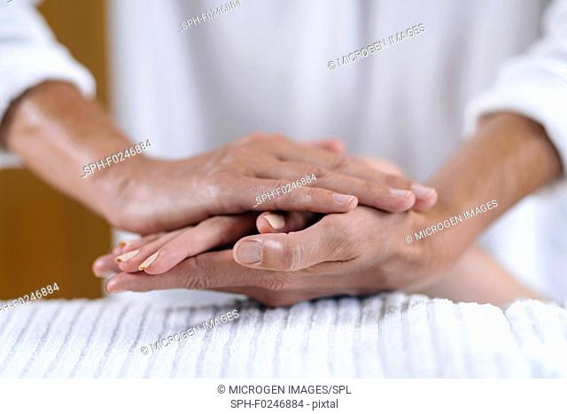 Reiki practitioner and patient holding hands at Reiki session. Energy healing concept