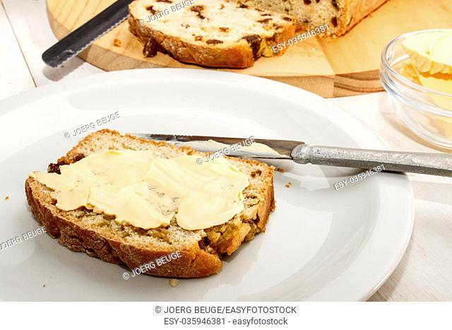 currant bread with butter on a white plate