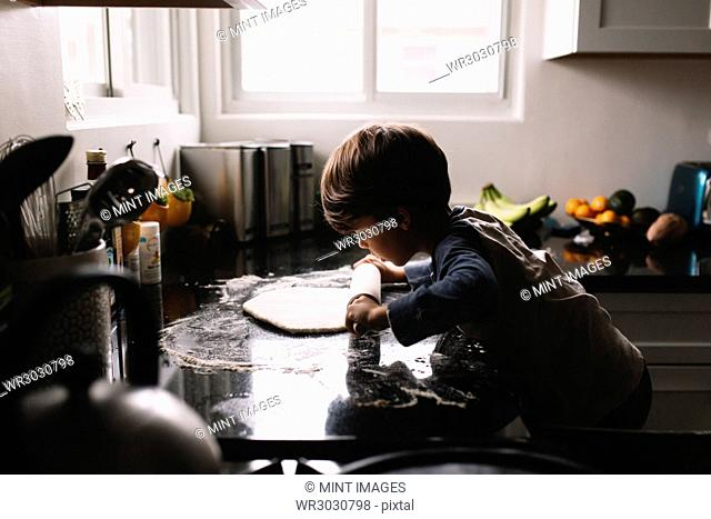 Young boy with brown hair standing in a kitchen, rolling out pizza dough with a wooden rolling pin