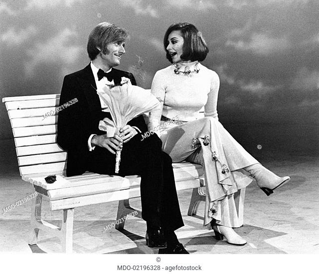 Dancer and presenter Raffaella Carrà sitting on a bench and receiving a bunch of flowers from Italo-French artist Nino Ferrer during the TV show Io, Agata e tu