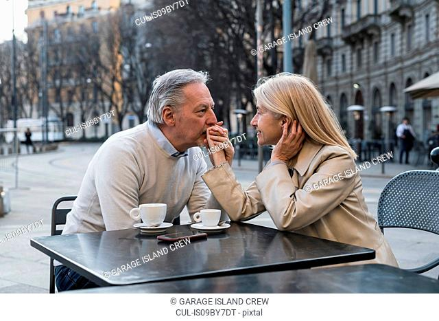 Senior man kissing woman's hand at cafe in city