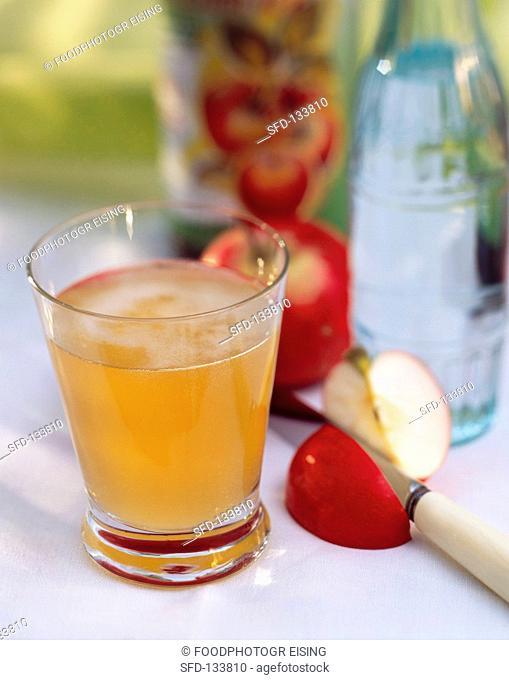 A glass of apple vinegar, décor: apple slice, bottle of water