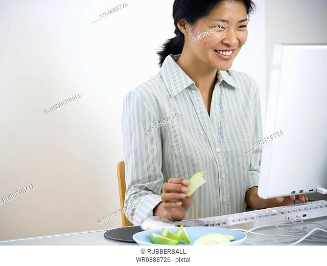 Mid adult woman sitting in front of a computer