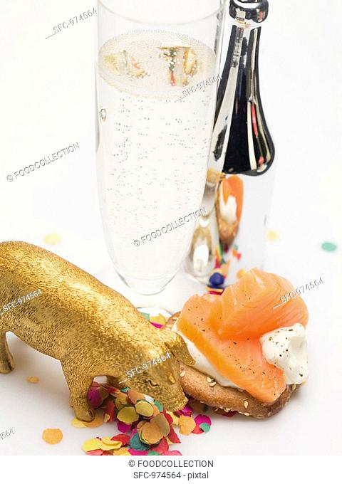 Glass of Prosecco, salmon appetiser, lucky pig & confetti
