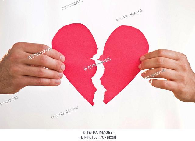 Two hands holding broken paper heart
