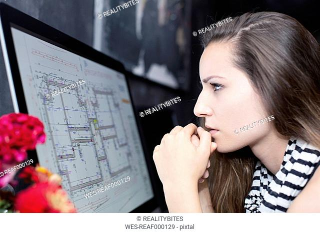 Young woman looking at construction plan on computer monitor