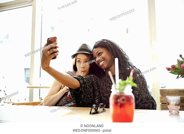 Two young women taking selfie in a cafe
