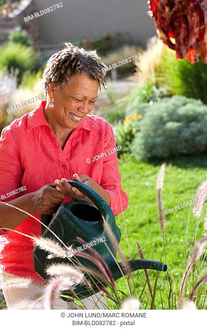 Black woman watering plants in garden